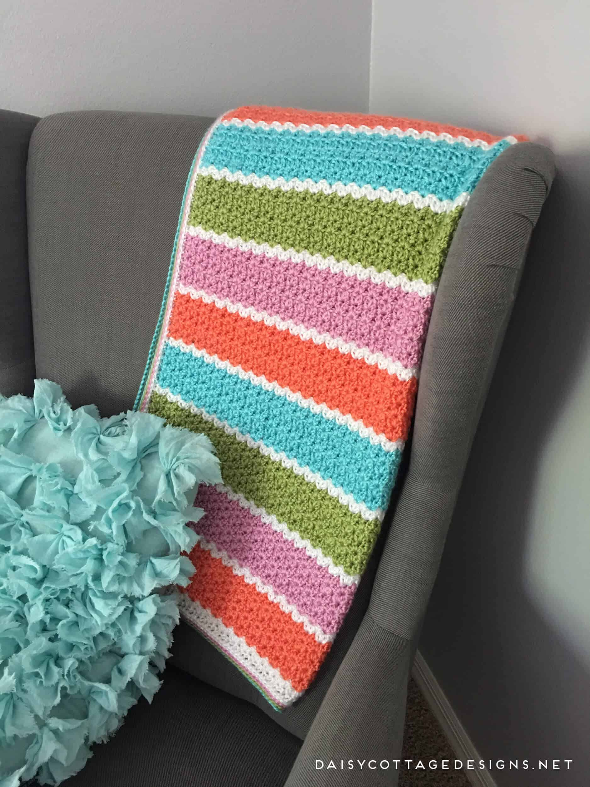 If you're looking for a free blanket crochet pattern that works up quickly, this easy v-stitch blanket from Daisy Cottage Designs is the way to go! | free crochet pattern, easy crochet blanket pattern, striped baby blanket pattern